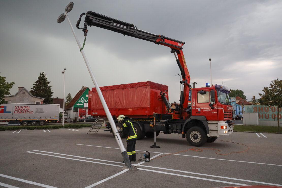 Lichtmast auf einem Parkplatz in Wels-Pernau droht nach Unfall umzustürzen