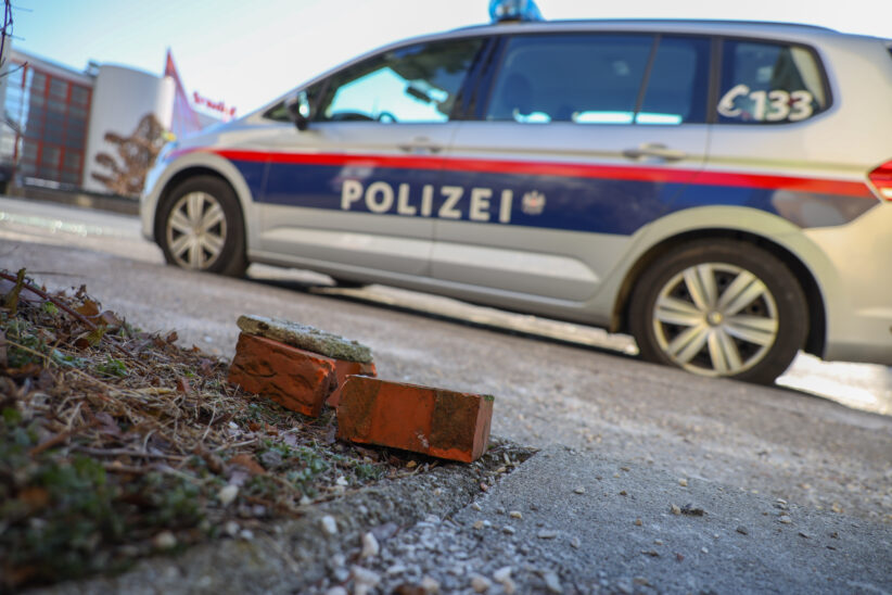 Polizeiautos vor Polizeiposten in Wels-Pernau mit Ziegelsteinen und Flaschen schwer beschädigt