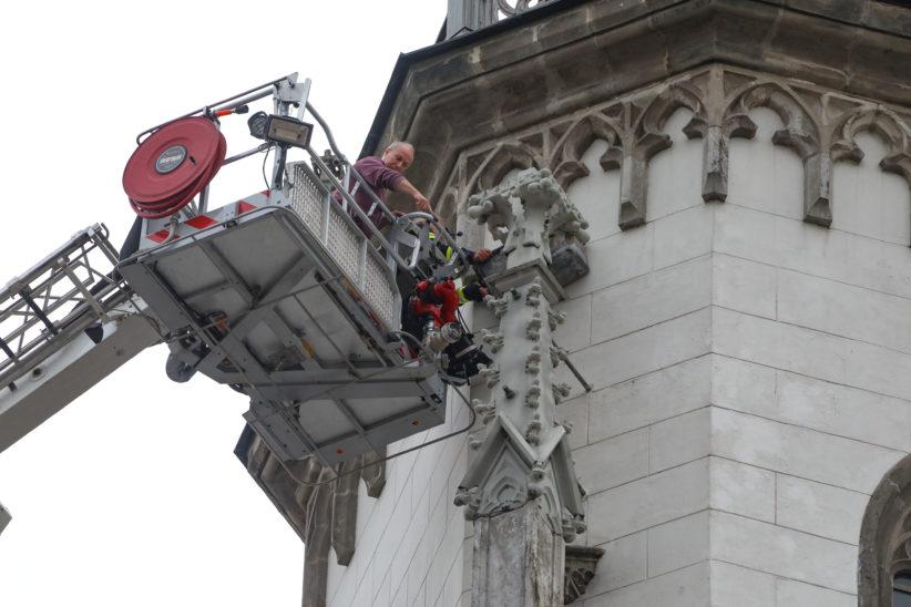 Loses Fassadenelement am Turm der Evangelischen Kirche in Wels-Innenstadt durch Feuerwehr gesichert